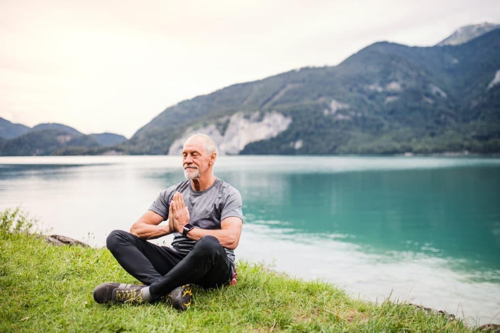 aged man feeling healthy sitting near a lake