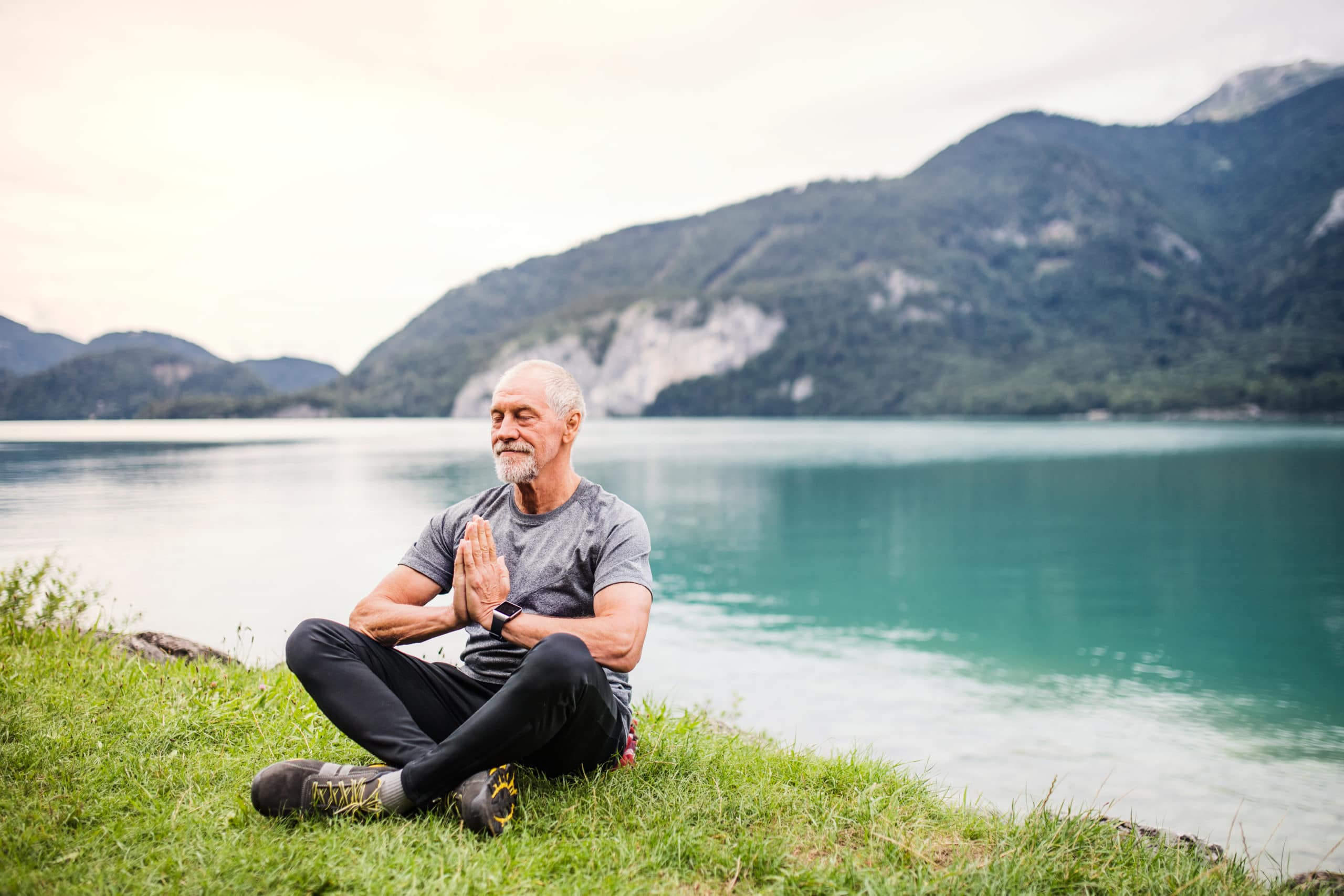 aged man feeling healthy sitting near a lake